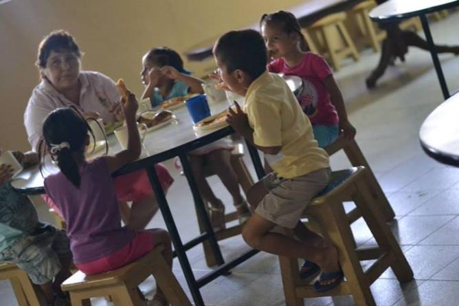Los niños de la Casa Hogar San José disfrutan de su 'café pendiente' y pan.  (Imagen: Facebook/RojoCaféGalería)